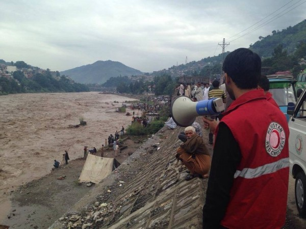 Photo: IFRC / PRCS  Pakistan. Azad Jammu and Kashmir, 2014 A response team member of the Pakistan Red Crescent Society issues an alert on a mega phone to people near the junction of Jhelum and Neelum rivers in Muzaffarabad district.