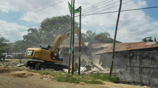 A bulldozer from Dar Es Salaam City Council pounds on a house that is illegally built in the city's flood prone Jangwani area in January 2016. TRF/Zuberi Mussa
