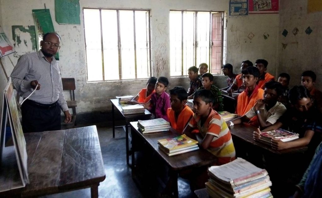 Monjurul Islam, head teacher of Char Bazra Uttarpara Primary School, in Bangladesh's northern Kurigram district, talks to his students about disasters and climate change. TRF/Mushfique Wadud